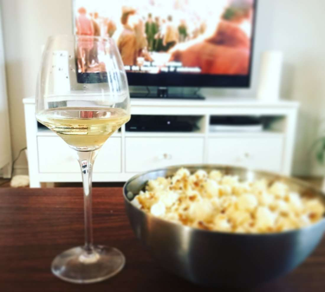 Vin, vinglas och popcornskål